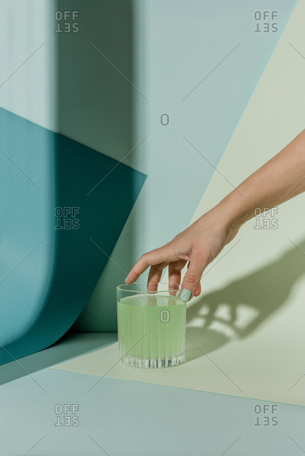 Woman's hand reaching for green cocktail on green and blue paper background