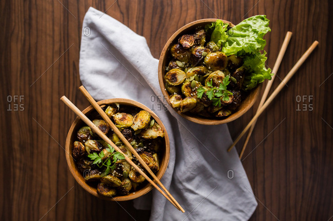 Two bowls filled with Brussels sprouts with chopsticks