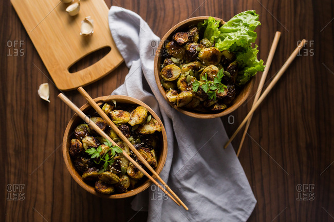 Overhead view of two bowls filled with Brussels sprouts with chopsticks