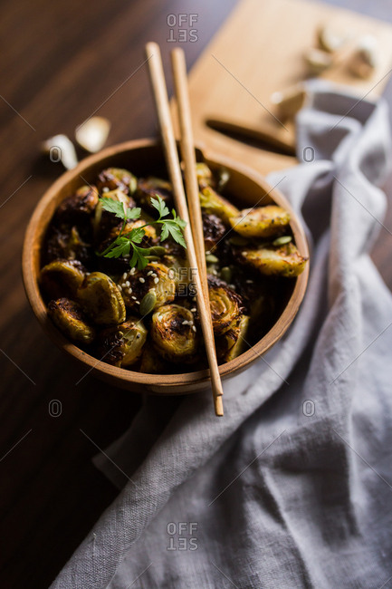 Close up of a bowl filled with Brussels sprouts with chopsticks