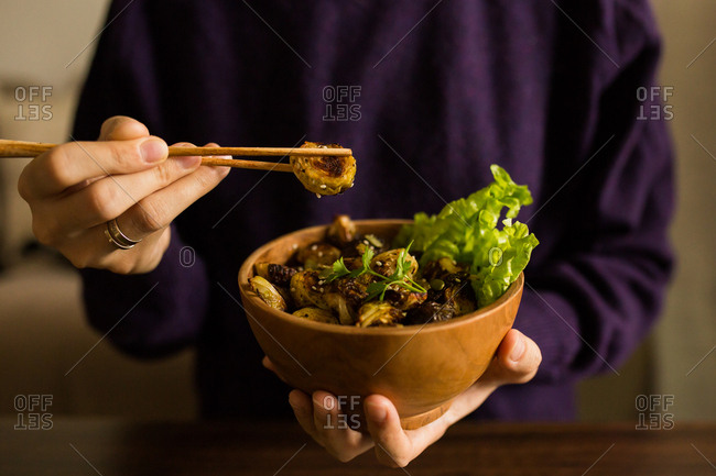 Woman eating Brussels sprout dish with chopsticks