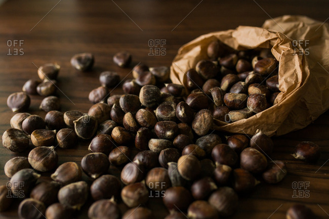 Bag filled with chestnuts spilled on wooden table