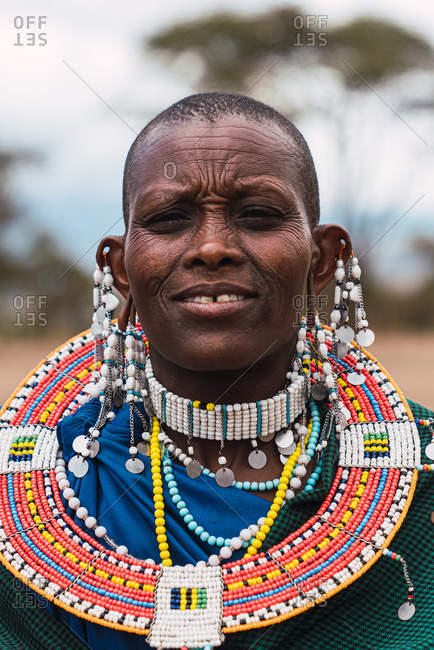 May 28, 2019: Masai woman wearing colorful beaded earrings and necklace in the savannah in Tanzania