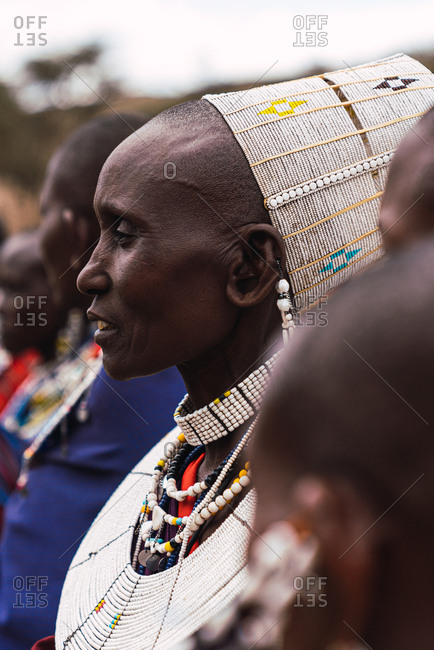 May 28, 2019: Profile of a Masai woman with ornaments and a hat with other women in Tanzania