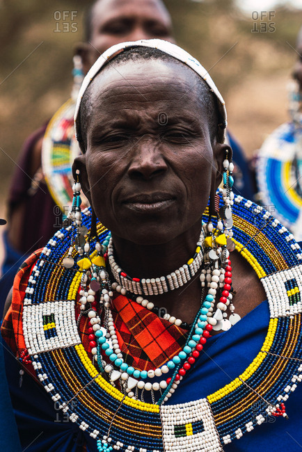 May 28, 2019: Masai woman with jewelry and looking straight ahead with other women in the background in Tanzania