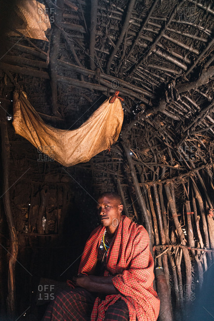 May 28, 2019: African Masai sitting inside a wooden cabin dressed in traditional clothes in Tanzania