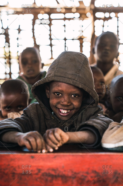 May 28, 2019: African boy with a hood smiling in front of a desk inside the school, Tanzania, Africa