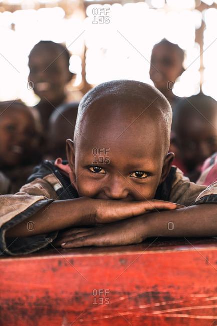 May 28, 2019: An African boy with his arms folded across a table at school, Tanzania