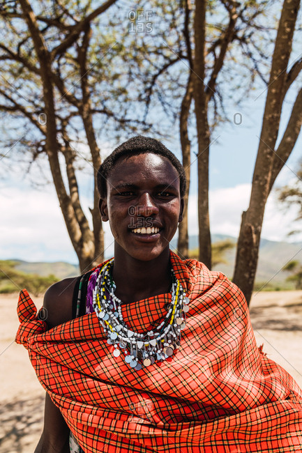 May 28, 2019: Young Masai boy smiling with traditional red dress on the savanna in Tanzania