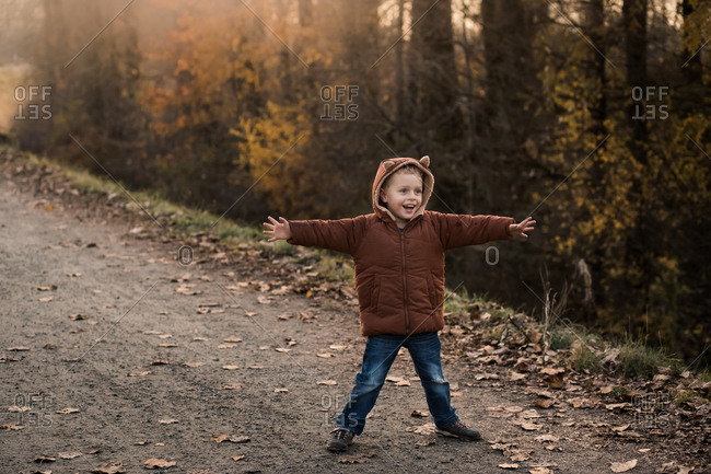Happy young boy wearing a fox coat standing on path with arms spread