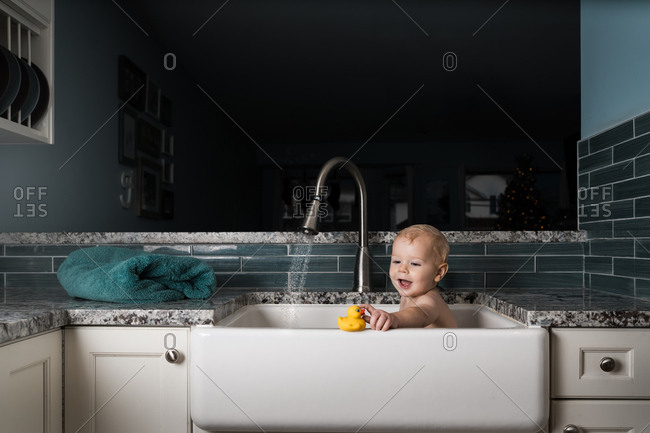 Baby taking bath in kitchen sink with rubber duck