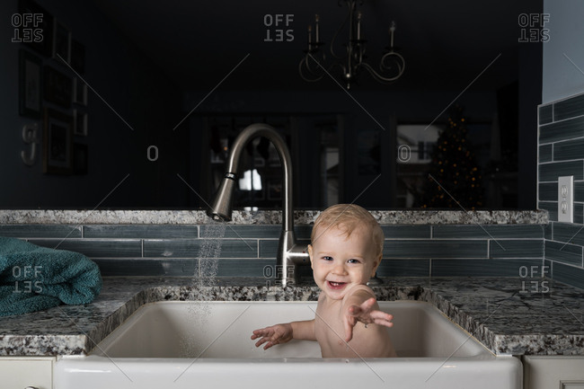 Baby taking bath in kitchen sink and reaching toward camera