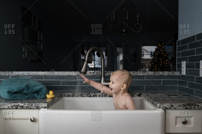 Baby taking bath in kitchen sink and reaching for rubber duck