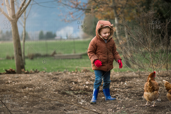 Young boy wearing fox coat looking at chickens