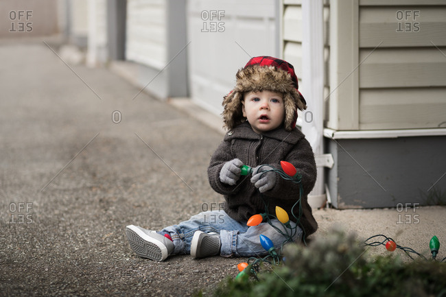 Baby boy sitting in driveway with Christmas lights