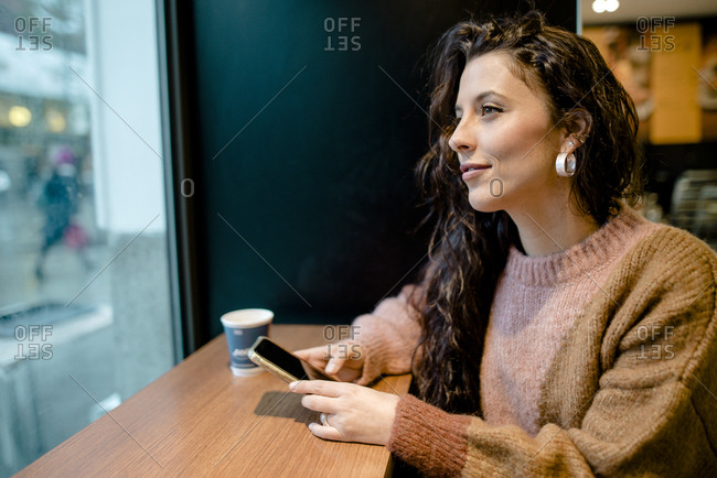 Woman using mobile phone inside a bar