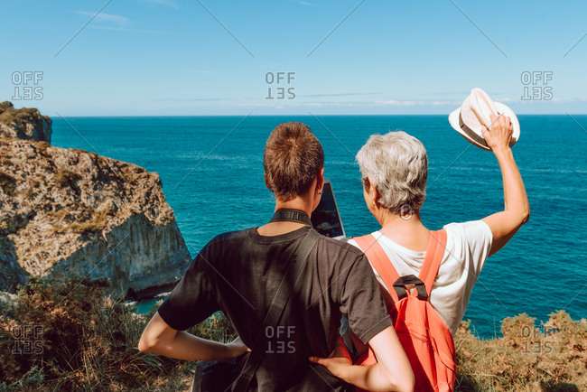 back view of touristic women exploring sightings at rocky coast with tablet in bright day