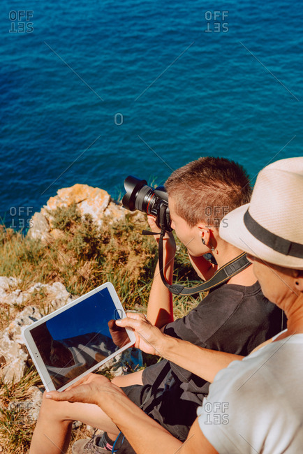 Side view of touristic women exploring sightings at rocky coast with tablet in bright day