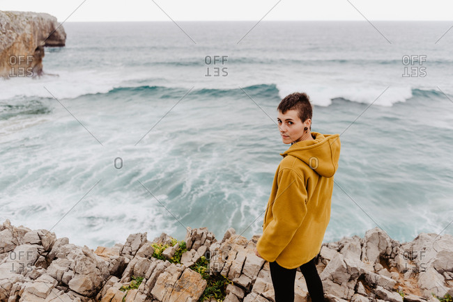 Back view of woman traveler in yellow warm hoodie standing alone on rocky shore with foamy waves on cloudy day looking at camera