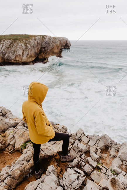 Back view of traveler in yellow warm hoodie standing alone on rocky shore looking at foamy waves on cloudy day