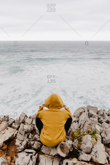 Back view of traveler in yellow warm hoodie sitting alone on rocky shore looking at foamy waves on cloudy day