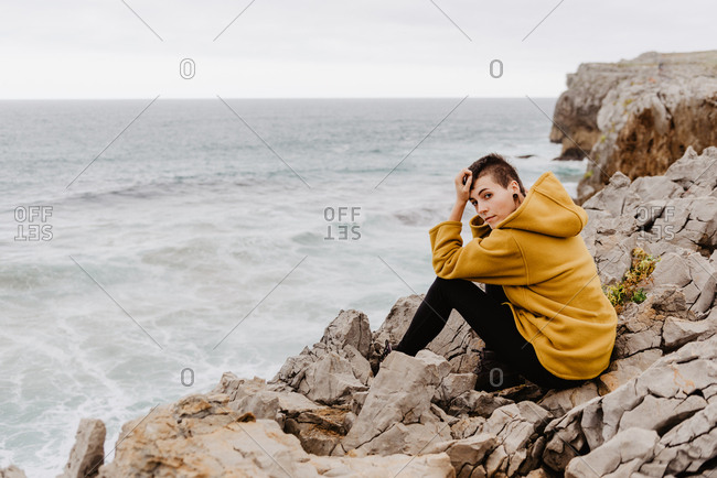 Side view of traveler woman in yellow warm hoodie sitting alone on rocky shore waves on cloudy day looking at camera