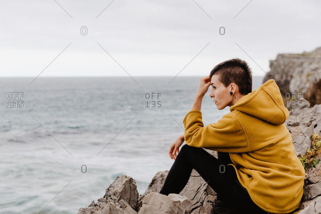 Side view of traveler woman in yellow warm hoodie sitting alone on rocky shore looking at foamy waves on cloudy day