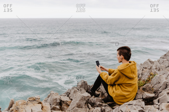 Back view of short haired unrecognizable woman in yellow sweatshirt sitting on rocky seashore above foamy wavy ocean and taking selfie on mobile phone on gray cloudy day