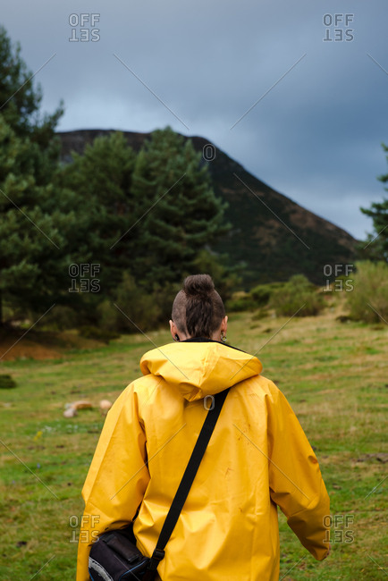 Person in yellow raincoat walking in forest