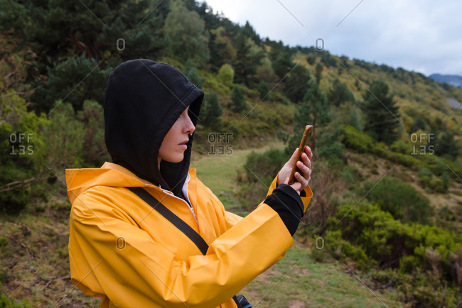 Woman in hoodie and yellow raincoat browsing smartphone