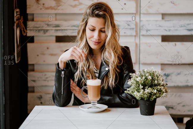 Long haired trendy beautiful blonde woman drinking from a glass of delicious foamy coffee with closed eyes