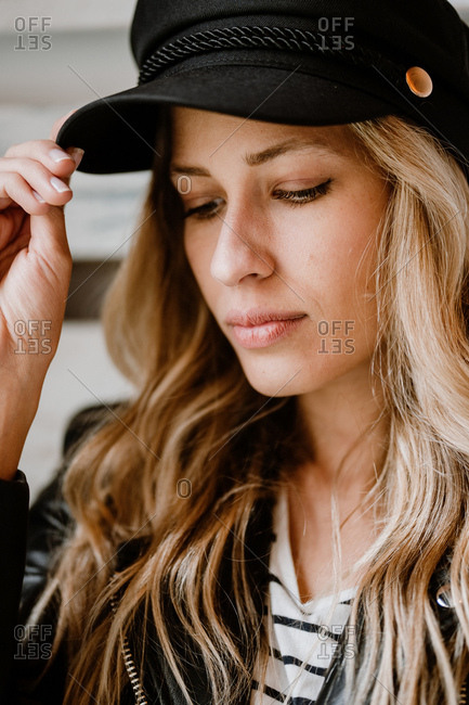 Stylish beautiful confident woman in leather jacket looking away while touching trendy black cap in her head on wooden wall