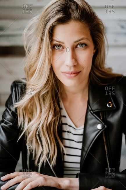 Stylish beautiful confident woman in leather jacket looking at camera on wooden wall