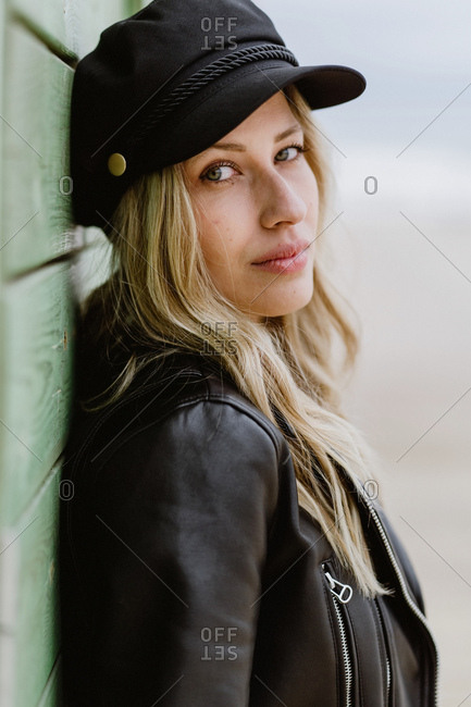 Trendy long haired blonde woman in black cap and leather jacket smiling brightly at camera and leaning on wall of wooden beach cabins