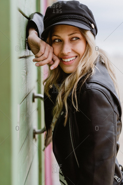 Trendy long haired blonde woman in black cap and leather jacket smiling brightly and leaning on wall of wooden beach cabins