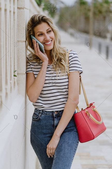 Happy cheerful young female in casual striped shirt and jeans standing next to building on city street and talking on smartphone