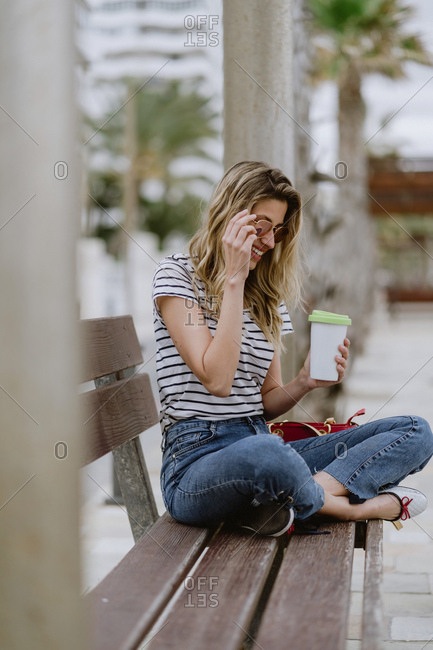 From above view of cheerful casual young female with takeaway cup of coffee sitting on city bench at seafront on summer day