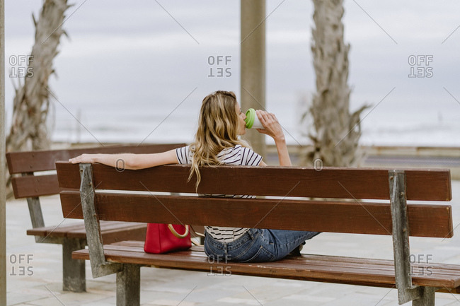 From behind view of cheerful casual young female with takeaway cup of coffee sitting on city bench at seafront on summer day
