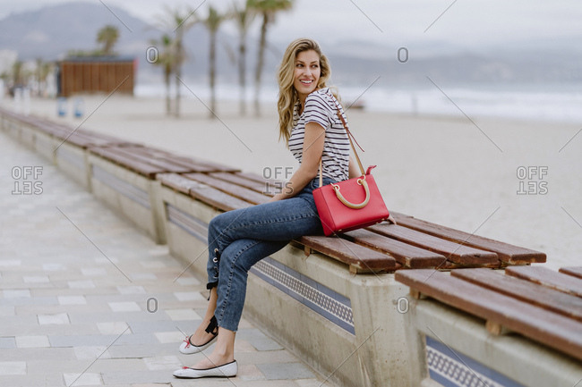 Attractive modern long haired blonde female with beautiful smile wearing casual striped shirt looking away while sitting at bench