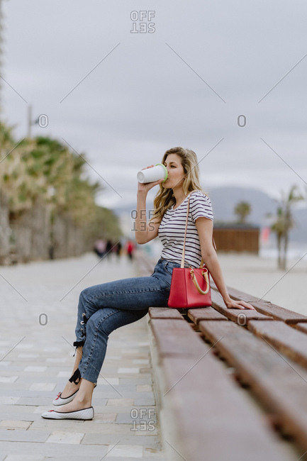 Side view of cheerful casual young female drinking from takeaway cup of coffee sitting on city bench at seafront on summer day