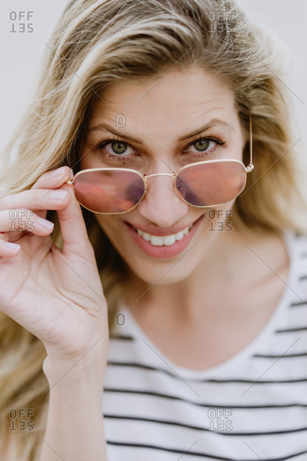 Attractive modern long haired blonde female with beautiful smile wearing casual striped shirt looking at camera over fashionable sunglasses