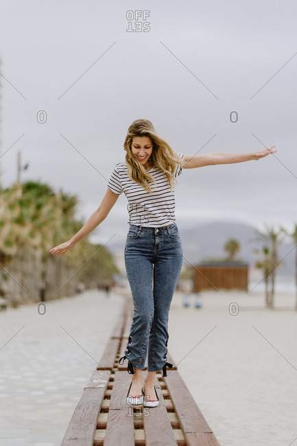 Happy cheerful female in casual clothes walking with arms spread on wooden bench and enjoying summer day at city seafront