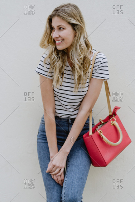 Charming young long haired blonde female with red shoulder bag wearing striped shirt and jeans standing with folded hands and looking away with shyly smile