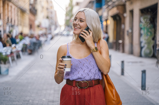 Blond lady in trendy summer outfit enjoying takeaway hot beverage and talking on smartphone while standing on blurred background of city street