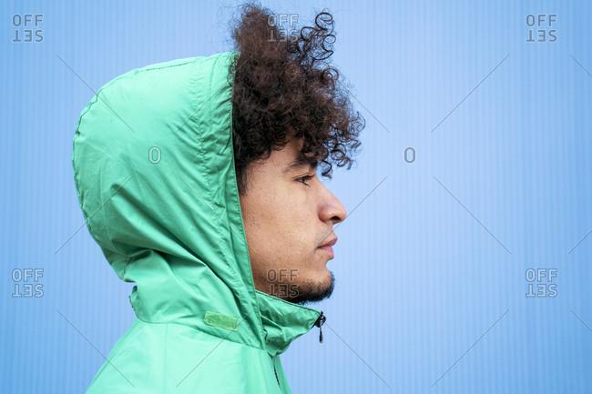Ethnic curly millennial man in green windbreaker looking away on blue background