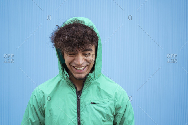 Ethnic curly millennial man in green windbreaker smiling brightly with closed eyes on blue background