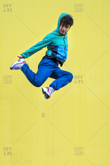 Cheerful curly ethnic male dancer in active blue wear jumping with crossed legs and covering face with hand on yellow background