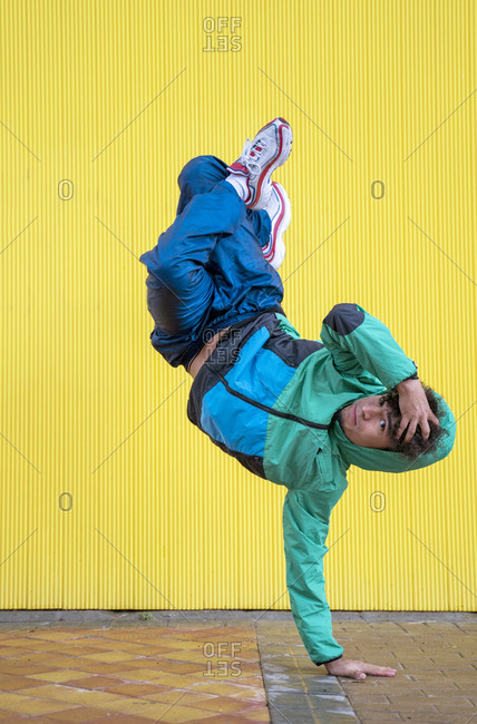 Cool curly male dancer in sportswear and sneakers doing handstands with cross legged against yellow wall on street