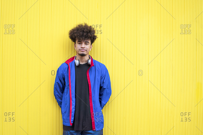 Ethnic cool guy with Afro hairdo in blue casual jacket with headphones on neck standing and looking at camera with yellow wall on background