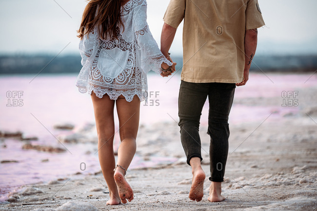 back view of crop adorable couple walking on an amazing pink lake of sea water and blue sky holding hands